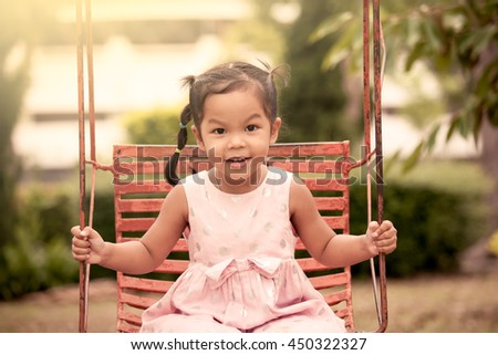 Child asian girl having fun to play swing in playground in vintage color tone - stock photo