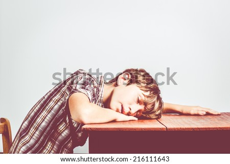 child asleep with head on the table - stock photo