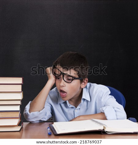 child at the table with books from school  - stock photo