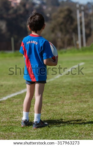 Child back with rugby ball - stock photo