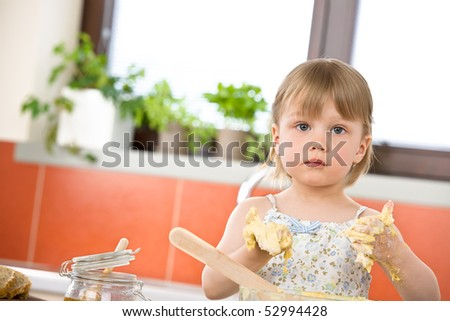 Child baking - little girl kneading dough in kitchen - stock photo