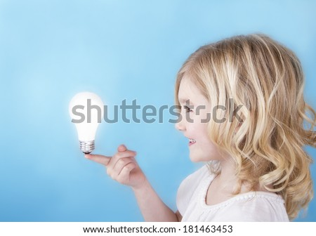 Child balancing a glowing light bulb on her finger with a blue background. - stock photo