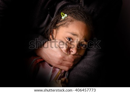 child being abducted over dark background - stock photo