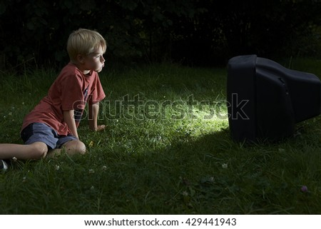Child blond boy watching TV horror / thriller outside in the garden at night - stock photo