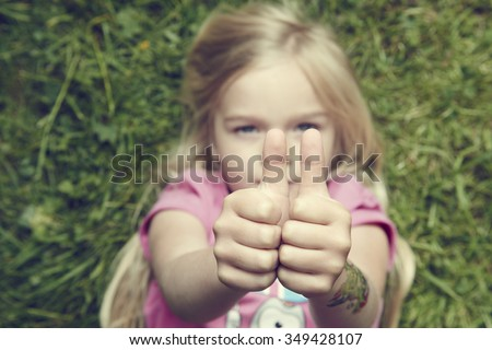 Child blond girl lying on green grass in summer park showing thumbs up gesture using both hand - stock photo