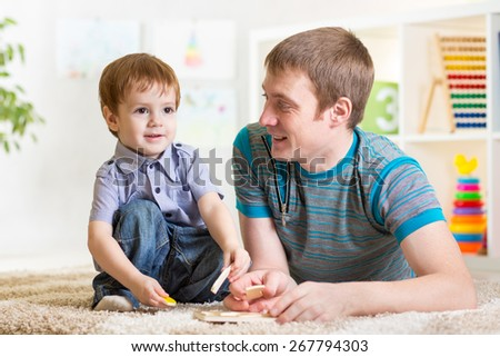 Child boy and father play with puzzle toy at home - stock photo