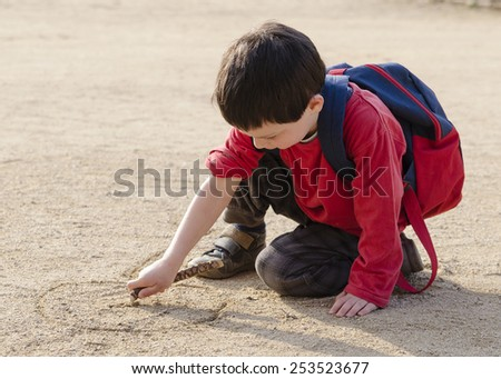 Child boy drawing into sand with a wood stick - stock photo