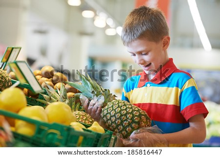child boy during shopping with pineapple fruit at supermarket - stock photo