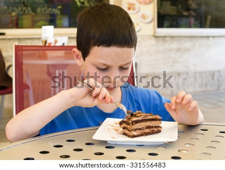 Child boy eating a slice of chocolate cake in a street cafe - stock photo