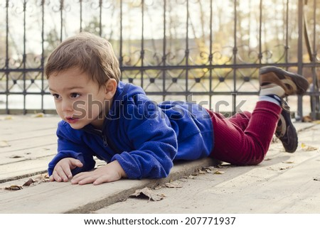 Child boy laying on a wooden floor ground on a bridge or landing in autumn or fall park outside.  - stock photo