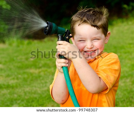Child, boy or kid plays with water hose outdoors during summer or spring to cool off in hot weather - stock photo