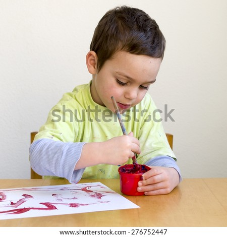 Child boy painting a picture with brush at home or school nursery. - stock photo