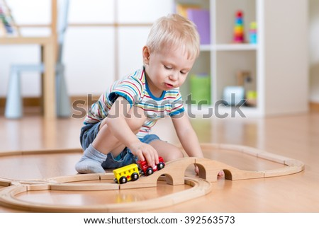 Child boy playing in his room with a toy train - stock photo