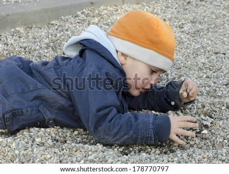 Child boy playing with pebbles or stones lying on ground.  - stock photo