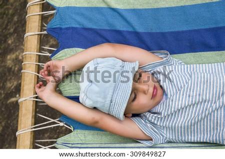 Child boy resting or sleeping in hammock in summer garden - stock photo