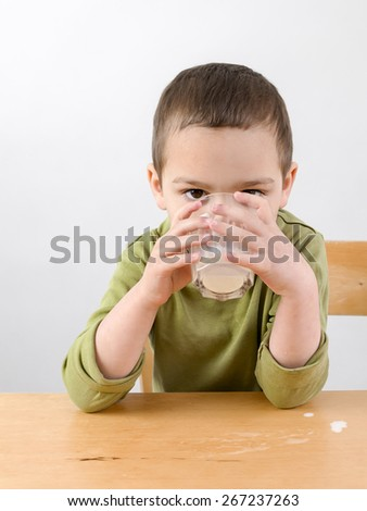 Child boy sitting at table, drinking milk from a glass. - stock photo