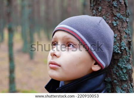 child boy thoughtful pensive alone forest wood - stock photo