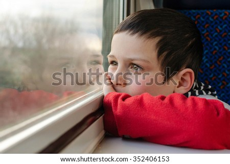 Child boy traveling by and looking from a window. - stock photo