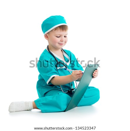 Child boy uniformed as doctor writing to clipboard - stock photo