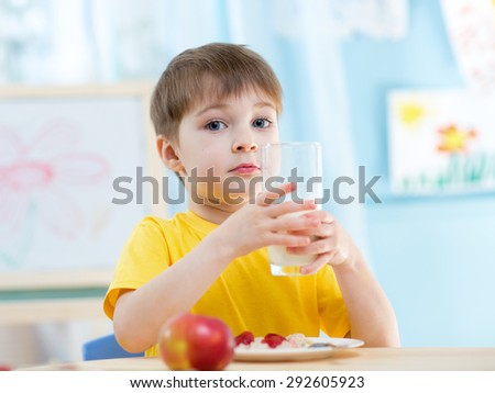 Child boy with a glass of fresh buttermilk - stock photo