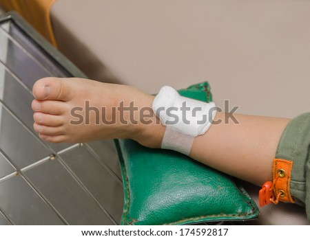 child boy with bandage on leg and lying down hospital bed. - stock photo