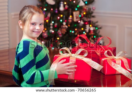 Child bringing Christmas presents with tree - stock photo