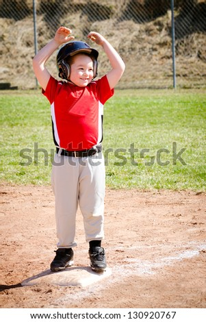 Child celebrates on base after making a hit during baseball game - stock photo