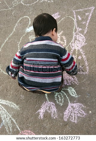 Child chalk drawing on the pavement outside.  - stock photo