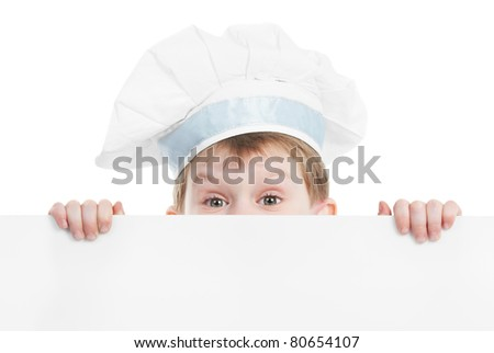 child chef in white uniform and hat hiding behind empty board isolated - stock photo