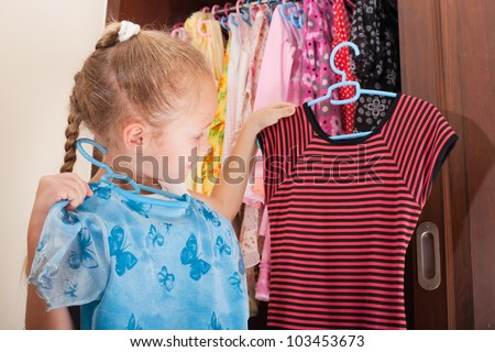 child chooses a dress from the wardrobe - stock photo