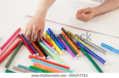 Child choosing a soft-tip pen, white background - stock photo