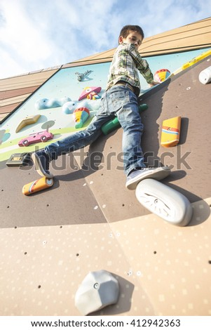 Child climb a climbing wall. Playground - stock photo