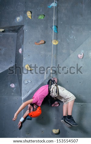 Child climbing on a wall in a climbing center. Fall of the Wall - stock photo