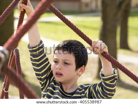 Child climbing rope ladder sport equipment in a park. - stock photo