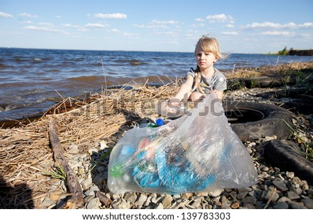 child collecting rubbish on the bank of river - stock photo