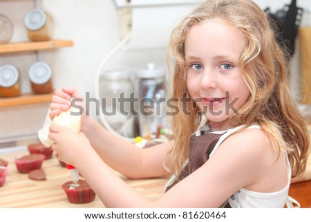 child cooking and helping decorate cupcakes - stock photo