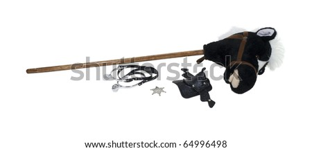 Child cowboy kit including spurs, sheriff star, saddle and a hobby horse - path included - stock photo