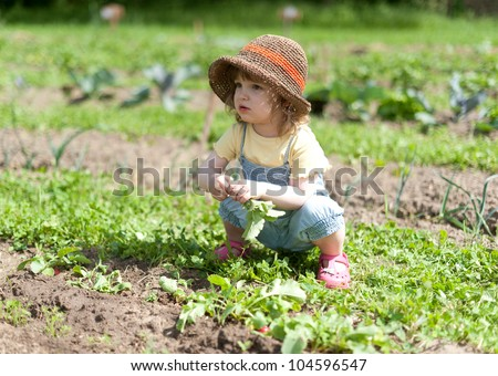 Child cowering in the vegetable patch - stock photo
