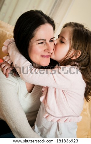 Child (cute girl) kissing her mother - indoors at home - stock photo