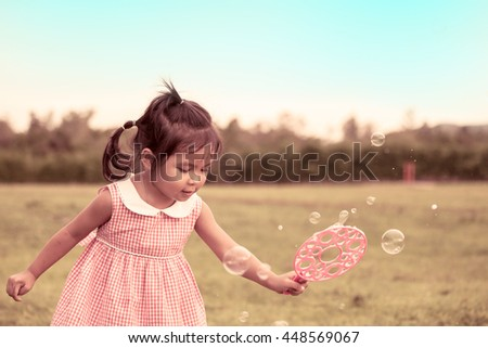 Child cute little girl having fun to play with her bubbles toy in the meadow in vintage color tone - stock photo