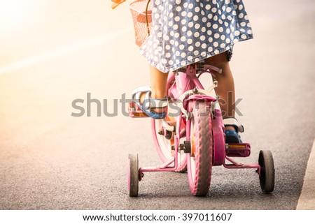 Child cute little girl riding bike in park - stock photo