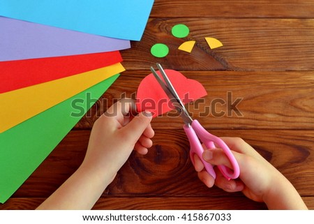 Child cuts a car out of paper. Sheets of colored paper. Kids art. Kids crafts. Crafts concept. How to make a greeting card father's day  - stock photo