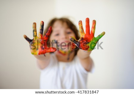 Child dirty of paint shows his dirty hands to the camera. Child has fun painting / drawing. Children's creativity. Art for baby. Emotions - stock photo