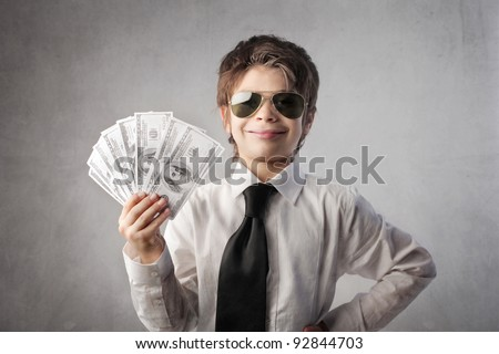 Child disguised as a rich businessman holding many banknotes - stock photo