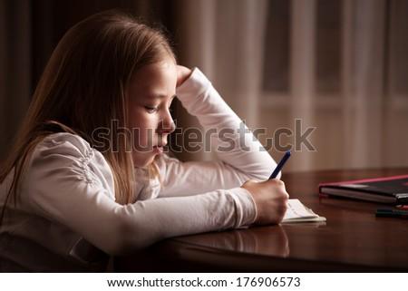 Child doing homework. Sad girl writing, reading - stock photo