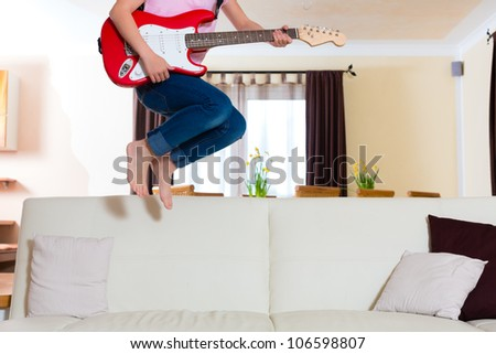 Child doing music jumping with guitar on the couch, only legs to be seen - stock photo