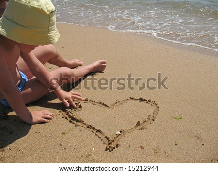 child draw heart on sand - stock photo