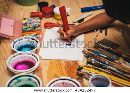 Child drawing at painting workshop. Painting tools on wooden board with sheet of white paper. Used colorful paintbrushes and crayons. - stock photo