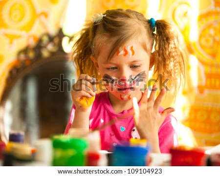 Child drawing paint with paint of face - stock photo