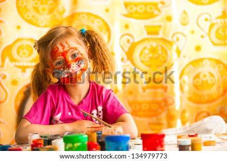 Child drawing paint with paint of face. - stock photo